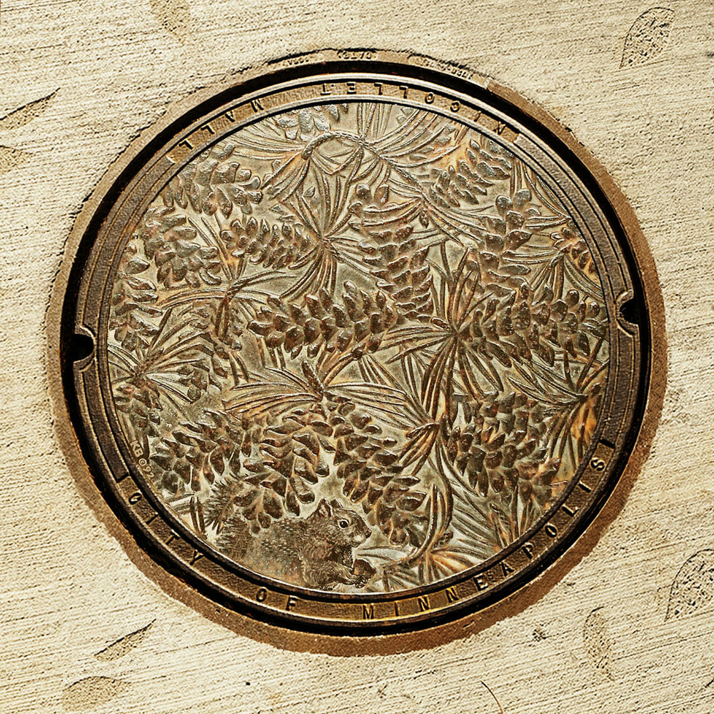 © 2018 Kate Burke. Norway PIne, manhole cover, when it was first installed, designed by Kate Burke.