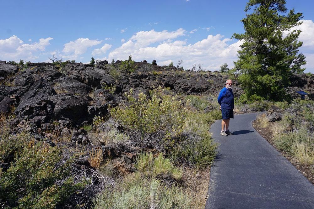 © 2018 Louise Levergneux. Michael on the walking path of Craters of the Moon National Monument & Preserve. /  Michael sur le sentier pédestre du Monument national et réserve de Cratères de la lune.
