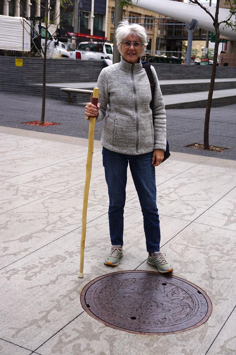 © 2018 Michael Sutton. Posing at the Walleye manhole cover designed by Kate Burke in Minneapolis. /  Debout devant la plaque d'égout conçus par l'artiste Kate Burke à Minneapolis.