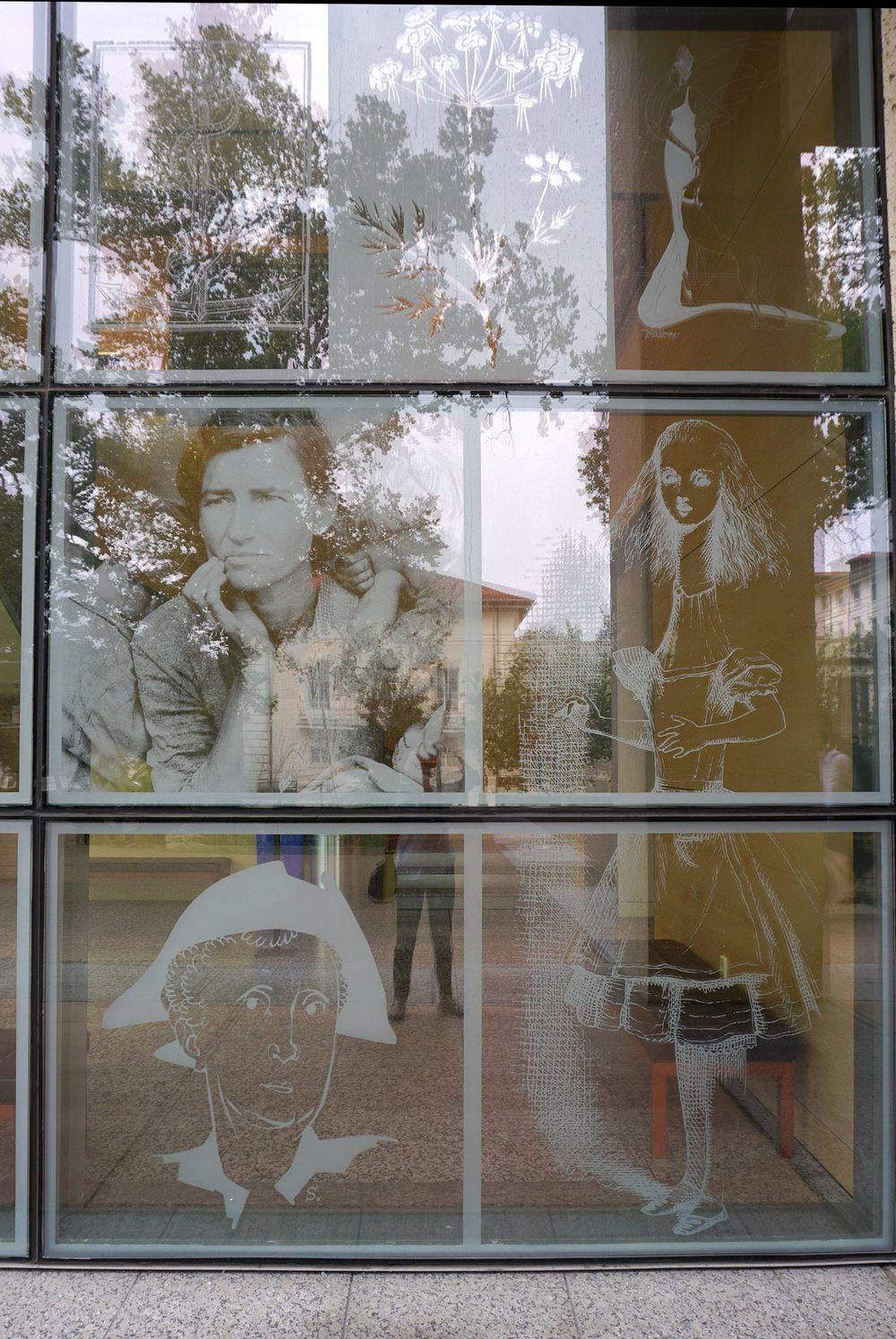 © 2018 Louise Levergneux. The Ransom Center's Southeast etched glass windows. Details: (middle left) Migrant Mother, Dorothea Lange, 1936, (right)   Illustration from Alice's Adventures in Wonderland, John Tenniel, 1865, (bottom left) Portrait of Marianne Moore, Robert Stewart Sherriff, 1960s.