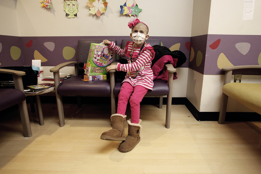 Angelina Sheena, 6, of Commerce Township, dons a big smile while showing off her toys from the Tons of Toys! event on Monday, December 11, 2012 at DMC Children's Hospital oncology unit in Detroit.