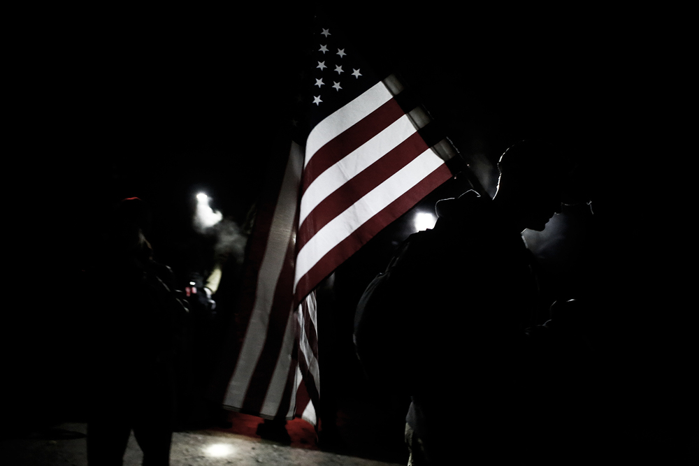 Cadre Tyler, a U.S. Army Special Forces member, holds the American flag and gives instructions to the GORUCK Challenge class on Friday, Sept. 13, 2013 in Ann Arbor.