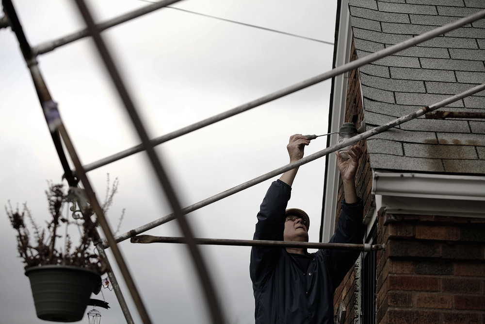 Nick DiNunzio removes the protective covering of a porch light on a home in his neighborhood on Monday, Oct. 28, 2013 in Detroit.  Tim Galloway / Special to DFP