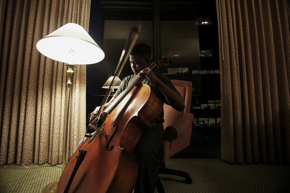 Sterling Elliott, 14, from Newport News, VA plays his cello in his hotel room at the Renaissance Marriott hotel on Tuesday, Feb. 18, 2014 in the GM Renaissance Building in Detroit, MI. /Tim Galloway for Al Jazeera America.