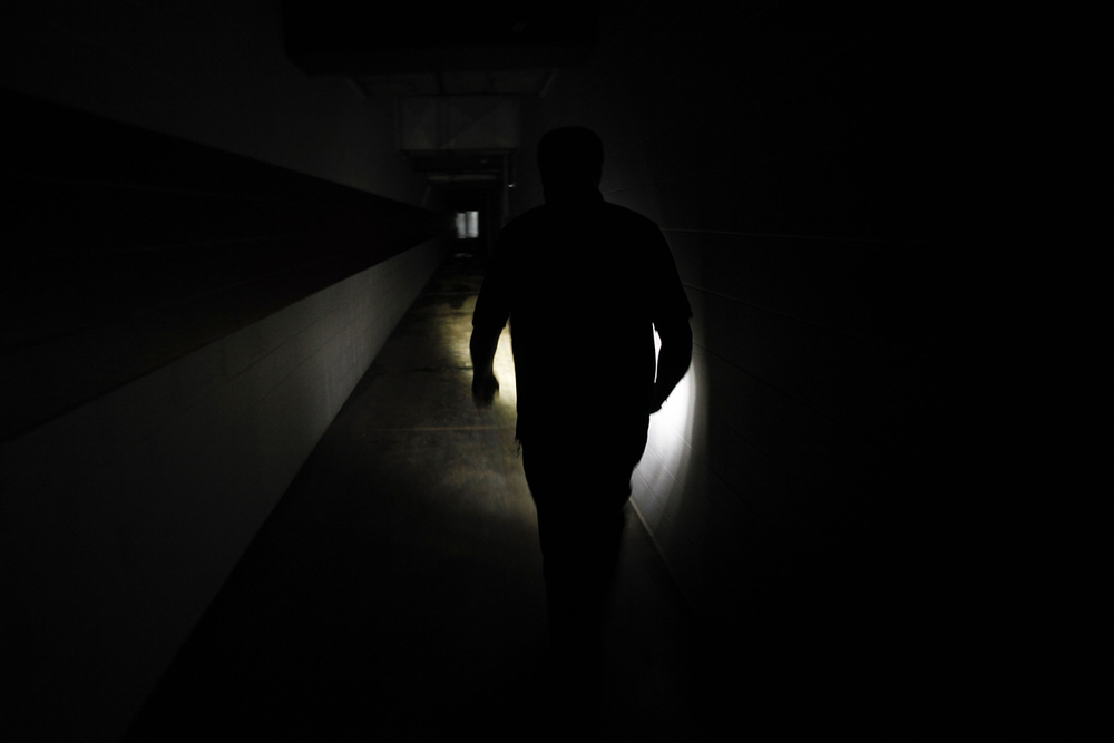 Jim Passeno, 58, from Commerce Twp. illuminates the way down a dark hallway to box suites at the Pontiac Silverdome on Friday, May 9, 2014 in Pontiac. Tim Galloway for Al Jazeera America