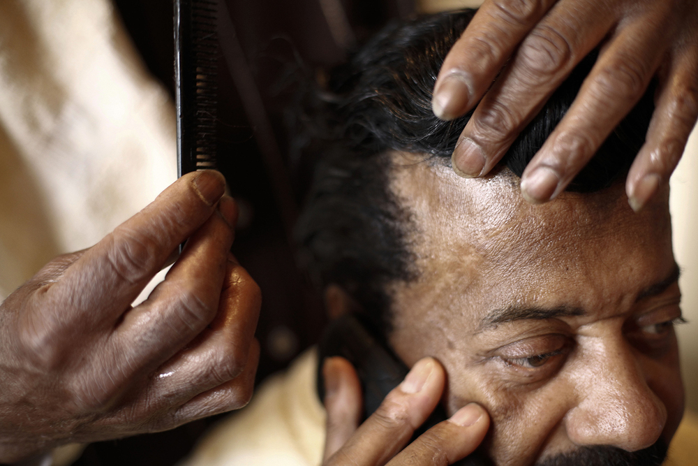 Walter McKinny, 60, from Detroit, speaks on the phone while receiving a comb-out from stylist Michael Horner, 66, on Saturday, May 3, 2014 Horner's  home in Detroit. Tim Galloway for Al Jazeera America