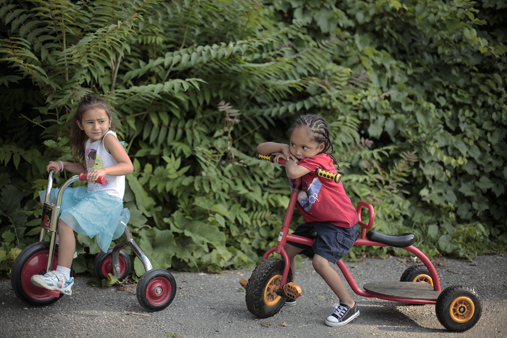 Ruby Cambray, 5, left, and Isaac Scott, 4, both from Pontiac, ride tricycles around the concrete path on the playground on Monday, Aug. 4, 2014 at Oakland Family Services in Pontiac. Tim Galloway/Special to DFP