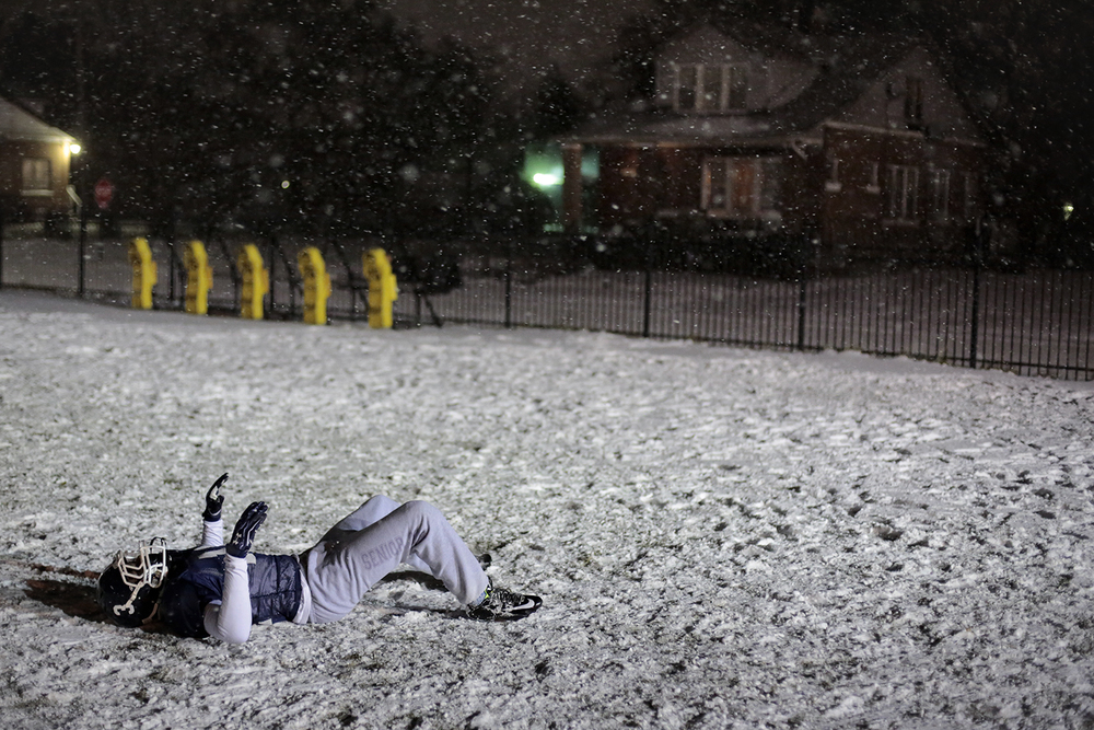 Blaine Woodland (Jr./DB-RB) lays on the snow at practice on Thursday, Nov. 20, 2014 at Loyola High School in Detroit.