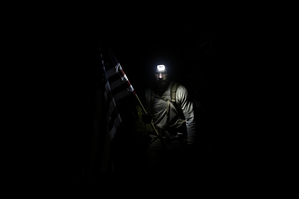 Cyril White from Chelsea stands in the dark holding the American Flag during GORUCK Challenge Class 771 on Saturday, September 14, 2014 in Ann Arbor.