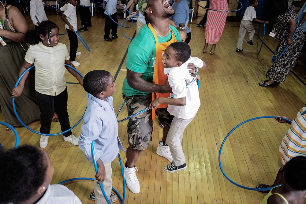 Detroit Lions linebacker Tahir Whitehead lifts James Montford, 8, right, from Detroit, out of their shared hula hoop at the Healthy Eating and Fitness Demonstration on Thursday, June 4, 2015 at Bagley Elementary School in Detroit. Tim Galloway for TheWEIGH