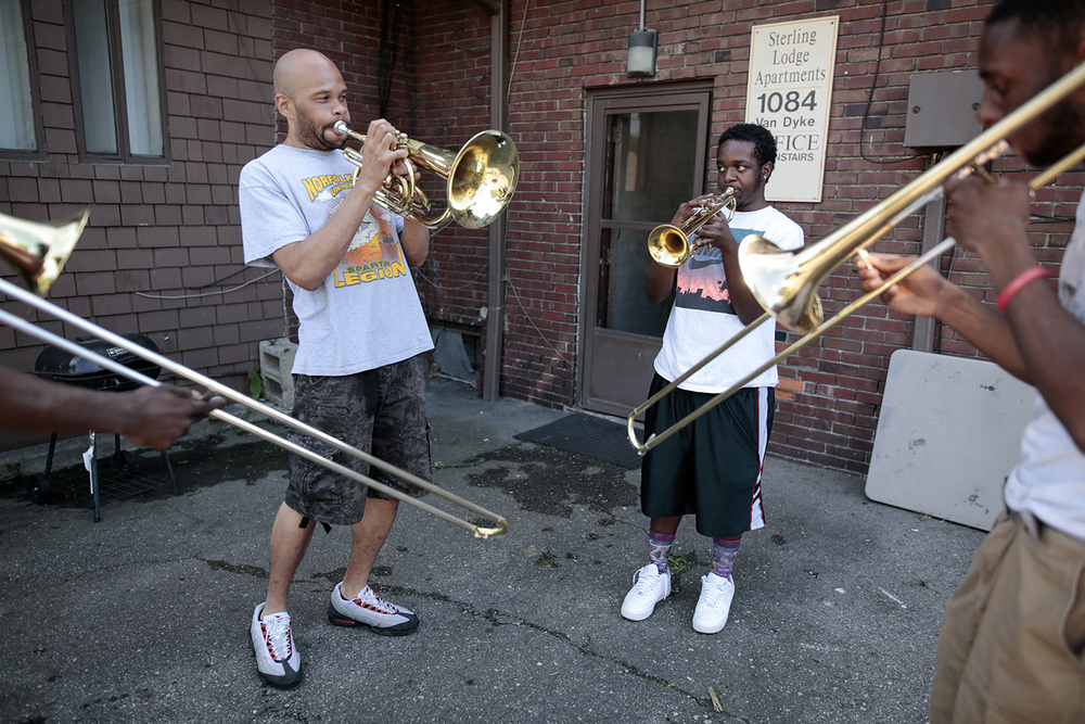 From left: Chris Gray, Dion Harvey and Otis Wynn practice playing in the parking lot of Gray's apartment on Tuesday, June 16, 2015 in the neighborhood of West Village in Detroit. Tim Galloway for Neighborhood Hub