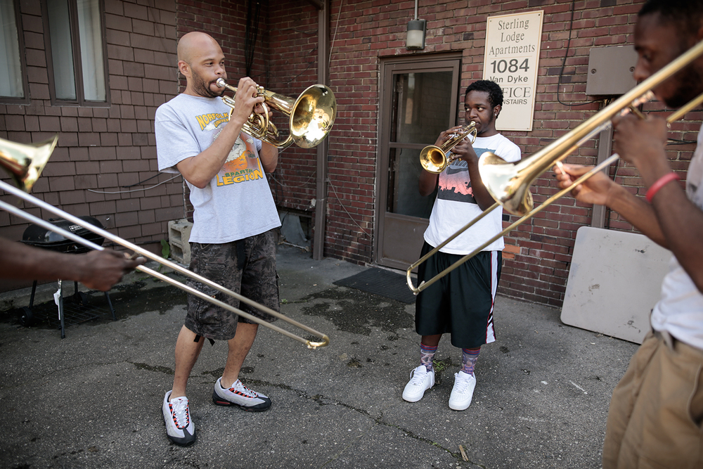 From left: Chris Gray, Dion Harvey and Otis Wynn practice playing in the parking lot of Gray's apartment on Tuesday, June 16, 2015 in the neighborhood of West Village in Detroit.