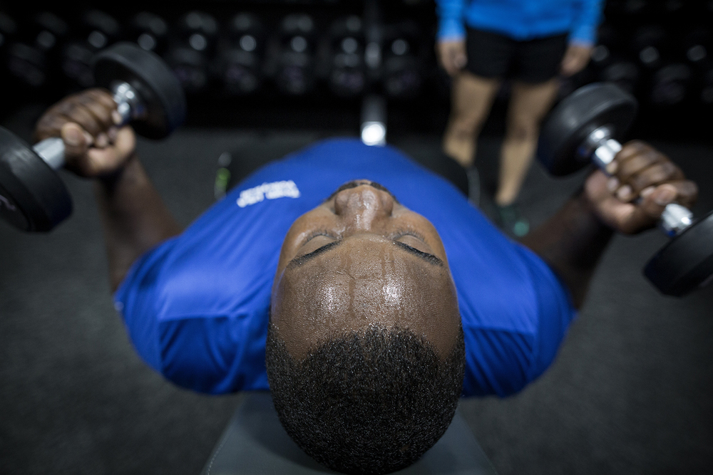 Grand Blanc, MI - Thursday, June 25, 2015: Athlete Michael Robinson from Grand Blanc, MI curls dumbbells during the team training session at Anytime Fitness in Grand Blanc, MI. The Michigan Special Olympics Volleyball Team has been preparing for the 2015 Special Olympics Summer Games in Los Angeles, CA beginning July 25. (Tim Galloway for ESPN)