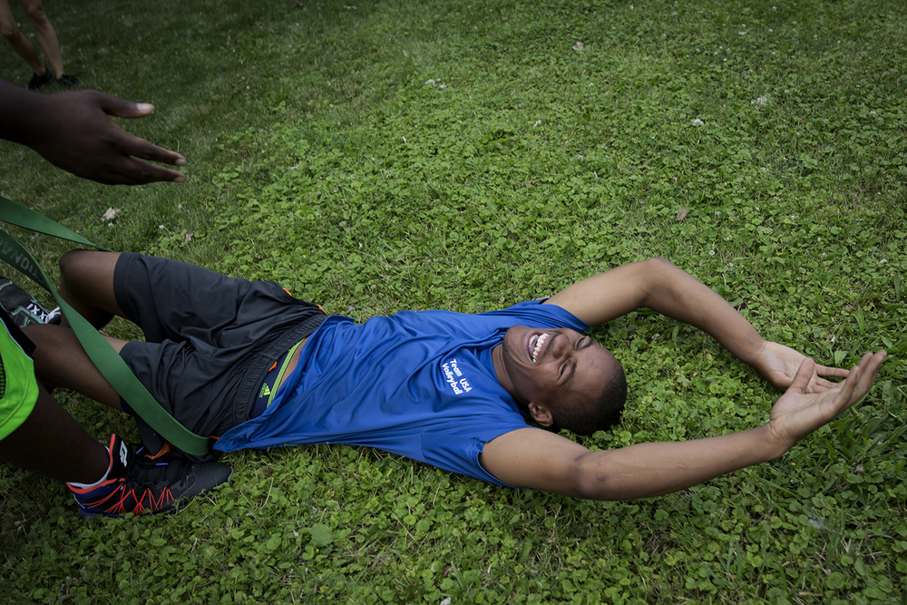 Grand Blanc, MI - Thursday, June 25, 2015: Athlete Dalvin Keller from Flint, MI laughs after collapsing on the ground during a resistance-band relay race on the lawn at Anytime Fitness in Grand Blanc, MI. The Michigan Special Olympics Volleyball Team has been preparing for the 2015 Special Olympics Summer Games in Los Angeles, CA beginning July 25. (Tim Galloway for ESPN)