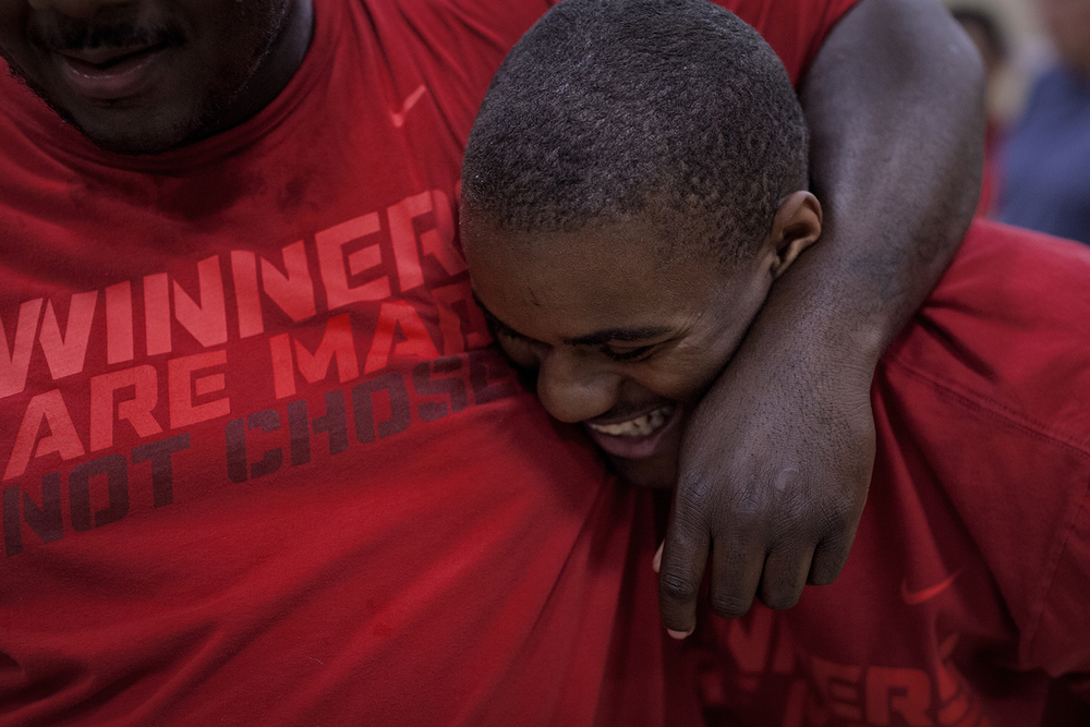 Flint, MI - Thursday, June 25, 2015: Dalvin Keller, center, from Flint, MI smiles as Michael Robinson from Grand Blanc, MI puts his arm around his during practice at the Elmer A. Knopf Learning Center in Flint, MI. The Michigan Special Olympics Volleyball Team has been preparing for the 2015 Special Olympics Summer Games in Los Angeles, CA beginning July 25. (Tim Galloway for ESPN)