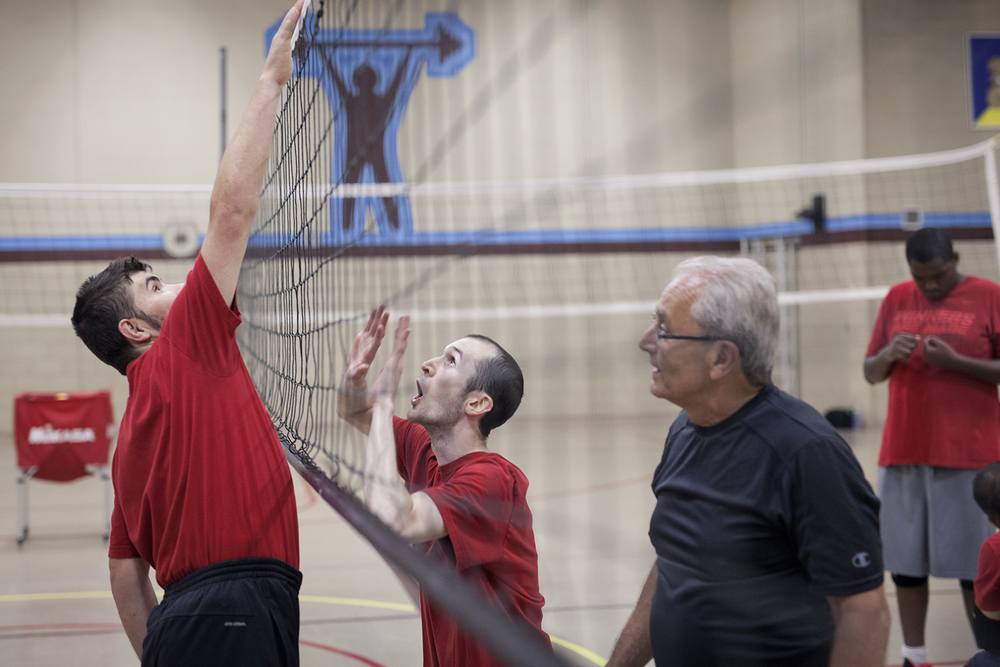 Flint, MI - Thursday, June 25, 2015: From left: Joe Gross from Montrose, MI pretends to spike a ball over the net as Brett Rife from Flint, MI attempts to block it while Coach Joe Finateri from Grand Blanc, MI watches during practice at the Elmer A. Knopf Learning Center in Flint, MI. The Michigan Special Olympics Volleyball Team has been preparing for the 2015 Special Olympics Summer Games in Los Angeles, CA beginning July 25. (Tim Galloway for ESPN)