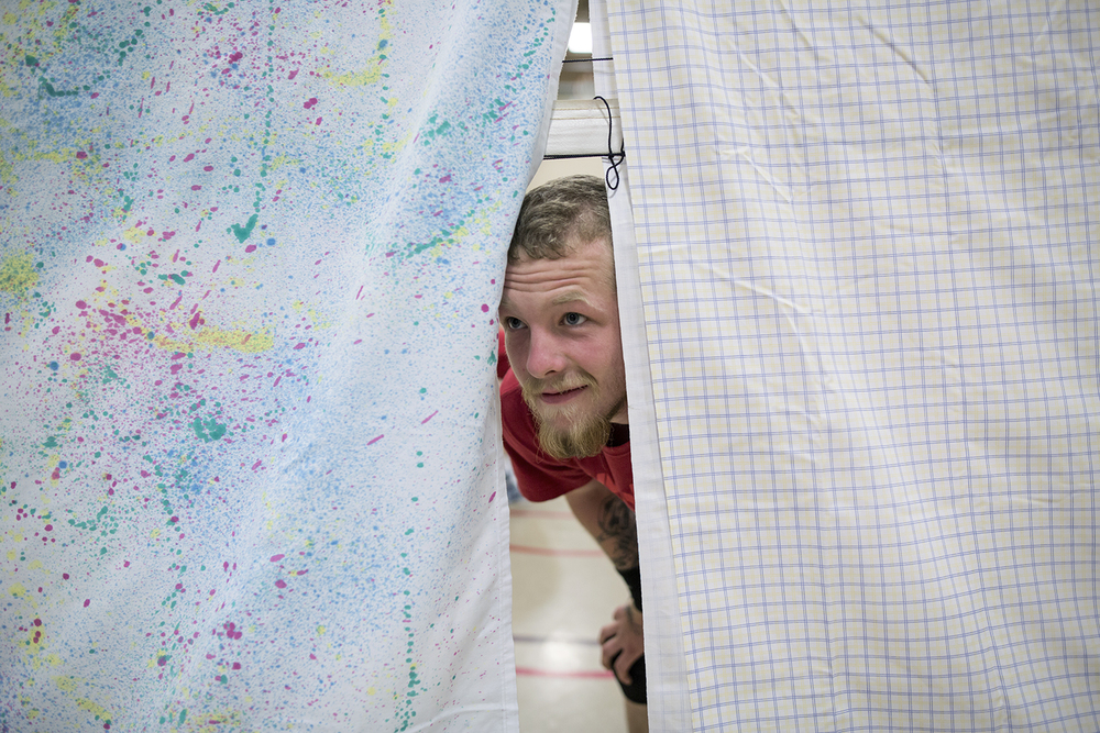 Flint, MI - Thursday, June 25, 2015: John Myers from Mt. Morris, MI peeks through the sheets draped over the net during practice at the Elmer A. Knopf Learning Center in Flint, MI. The Michigan Special Olympics Volleyball Team has been preparing for the 2015 Special Olympics Summer Games in Los Angeles, CA beginning July 25. (Tim Galloway for ESPN)