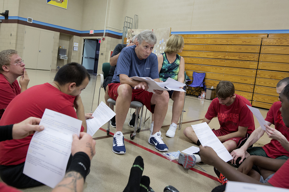 Flint, MI - Thursday, June 25, 2015: Coach Sheila Gafney from Grand Blanc, MI, center, goes over paperwork for the upcoming trip to Los Angeles, CA with the team after practice at the Elmer A. Knopf Learning Center in Flint, MI. The Michigan Special Olympics Volleyball Team has been preparing for the 2015 Special Olympics Summer Games in Los Angeles, CA beginning July 25. (Tim Galloway for ESPN)