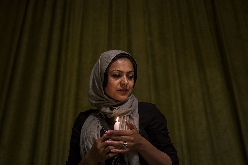 "Dearborn Heights resident Sara Syeda carefully holds a candle after helping light a small arrangement of candles forming the word ""peace"" before a vigil on Thursday, June 16, 2016 at the Islamic House of Wisdom in Dearborn Heights. Tim Galloway/Special to DFP"