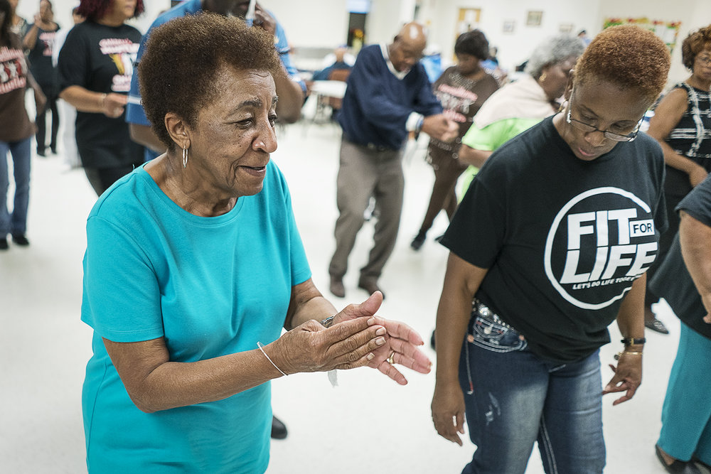 "Flint, MI - Tuesday, October 24, 2017: Flint residents Ruth Morris, left, 82, and Queenella McGee, 66, right, dance together at the Hasselbring Senior Community Center. Both women come for the dancing and the people. ""I love coming because of these people,"" Morris says, ""they're my sisters and brothers.""