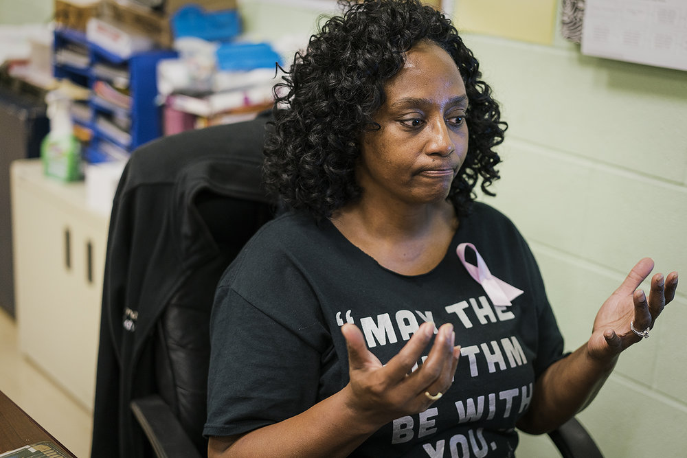 "Flint, MI - Monday, October 16, 2017: ""You cry and you keep going, you know?"" Sheila Miller-Graham, from Flint,  sits at her desk in her classroom at Flint Northwestern High School and holds her hands up in futility. Over the years, Miller-Graham has had more and more students die due to violence in the city, which she believes is getting worse. Having written multiple obituaries for students, she hopes that the lessons she teaches through dance help keep her students away from a lifestyle that could potentially result in harm or death.