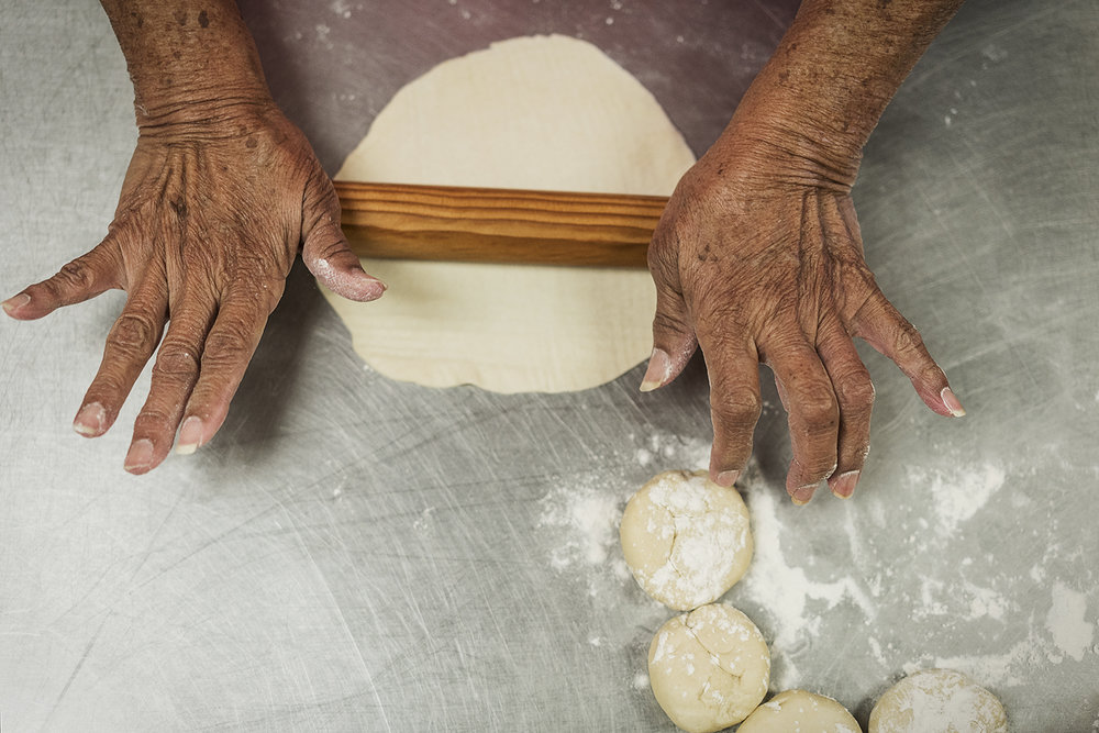 Flint, MI - Tuesday, October 17, 2017: Ofelia Luna, 79, from Flint, rolls out masa on the countertop in the kitchen of the San Juan Diego Activity Center at Our Lady of Guadalupe, in very much the same way she has since 1958, only a year after the tradition began. Each Tuesday, ladies from the parish meet to make homemade tortillas for the community meal after Sunday morning mass.