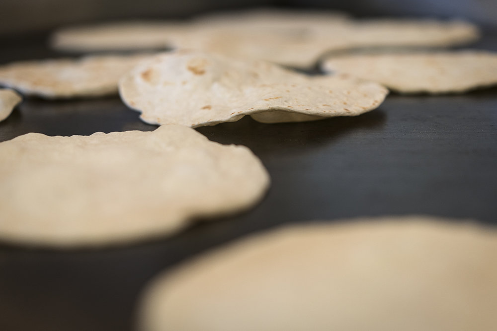 Flint, MI - Tuesday, October 17, 2017: Homemade flour tortillas bubble and brown on the cooktop in the kitchen at the San Juan Diego Activity Center at Our Lady of Guadalupe. Approximately 60-80 pounds of flour are used each week to make tortillas for the parish's community meal on Sundays after morning mass and to be sold to generate funding for the church.