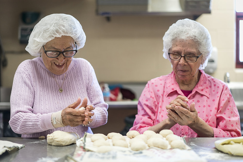 Flint, MI - Tuesday, October 17, 2017: Linda Quintanilla, 90, left, from Flushing, laughs as she rolls balls of masa and chats with Connie Aguilar, right, 81, from Flint, in the kitchen of the San Juan Diego Activity Center at Our Lady of Guadalupe. Each Tuesday, the ladies get together to form The Tortilla Factory and churn out dozens of tortillas to be used for the church's community meal after Sunday morning mass, and to be sold to generate funding for the church.