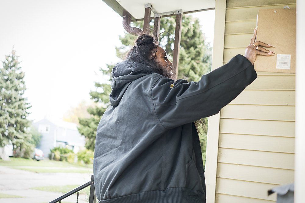 Flint, MI - Wednesday, October 25, 2017: Gently rapping on the storm door, Flint resident Shadae Johnson, 26, waits for someone to answer. Johnson approaches 60 - 70 homes each day on the delivery route with her team, requesting signatures and documenting the amount of water each home is supplied with. 