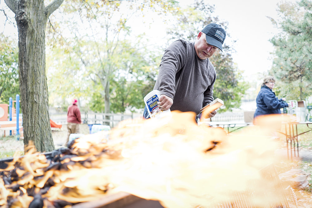 Flint, MI - Saturday, October 28, 2017: Volunteer and Davison resident Steven Moore, 52, squeezes lighter fluid onto a pile of charcoal briquettes as he prepares the grill for the Flint Community Cookout. Moore, and other volunteers, will prepare some of the food at the cookout while other volunteers and participants of the cookout will bring dishes of their own to share.