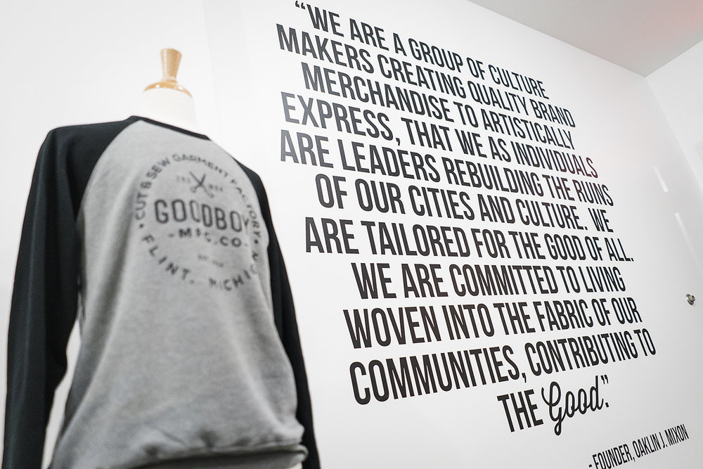 Flint, MI - Monday, November 13, 2017: Vinyl graphics, photographs and other decorations are hung on the walls of the new GoodBoy Clothing showroom in preparation for the upcoming grand opening event on Friday, November 17, 2017 at GoodBoy Clothing in downtown Flint.