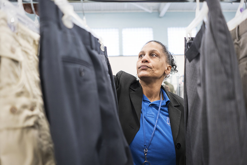 Flint, MI - Monday, December 18, 2017: Community Closet Coordinator at the Catholic Charities Center for Hope Redonna Riggs, 47, of Flint, organizes donated clothing hanging from a clothing rack.