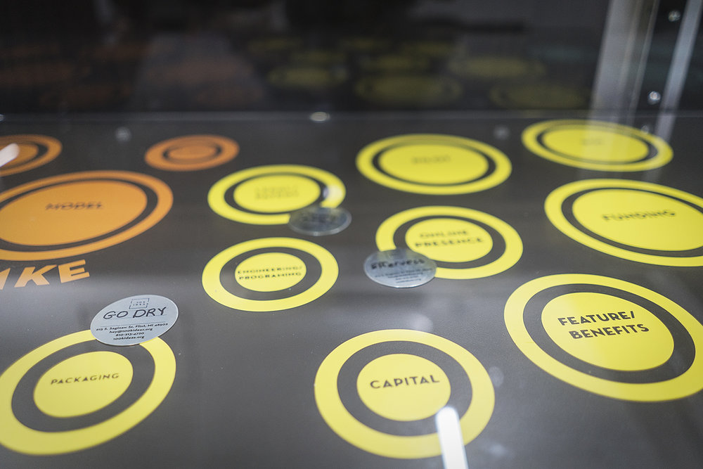 Flint, MI - Friday, December 22, 2017: The game board at 100k Ideas in the Ferris Wheel Building downtown, tracks the progress of innovators' ideas as they work closer to going to market.