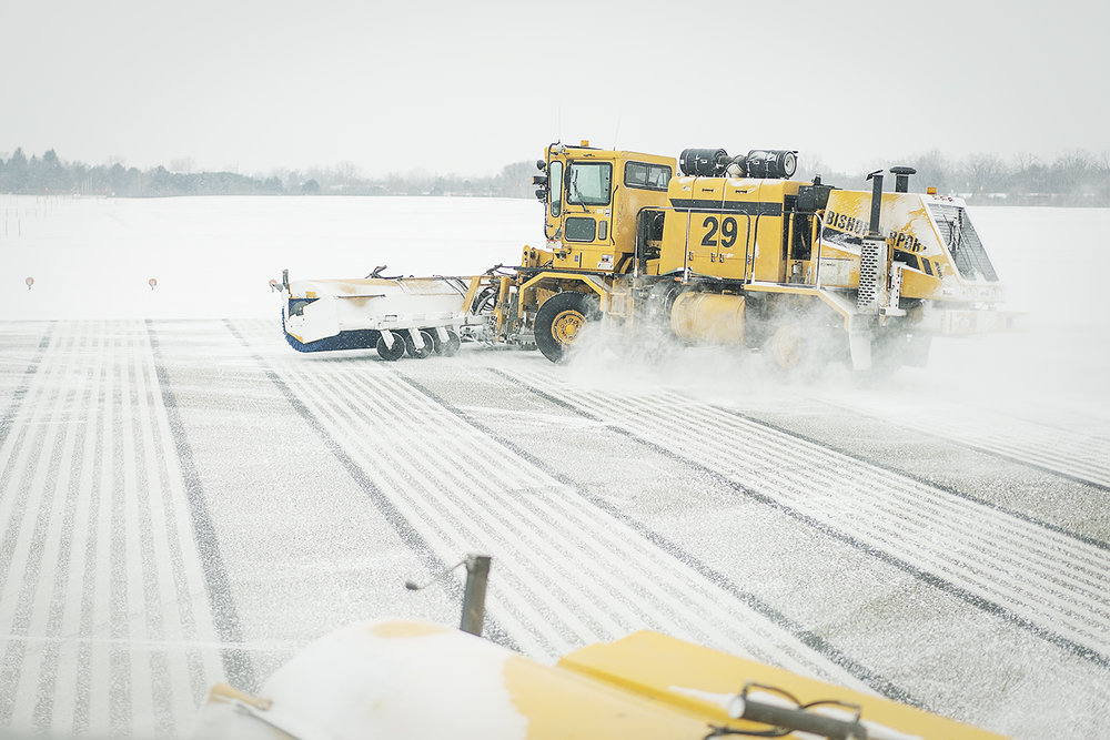 Flint, MI - Wednesday, January 3, 2018: A broom truck, using massive brushes and a blower clears snow from the runway at Bishop International Airport.
