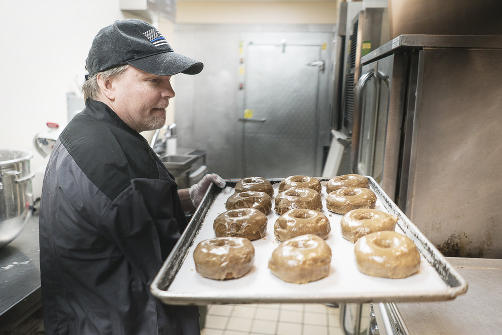 Flint, MI - Thursday, January 4, 2018: Bruce Sowles, 53, of Flint, carries a tray of fresh donuts to prepare them for delivery at Blueline Donuts, inside of Carriage Town Ministries.