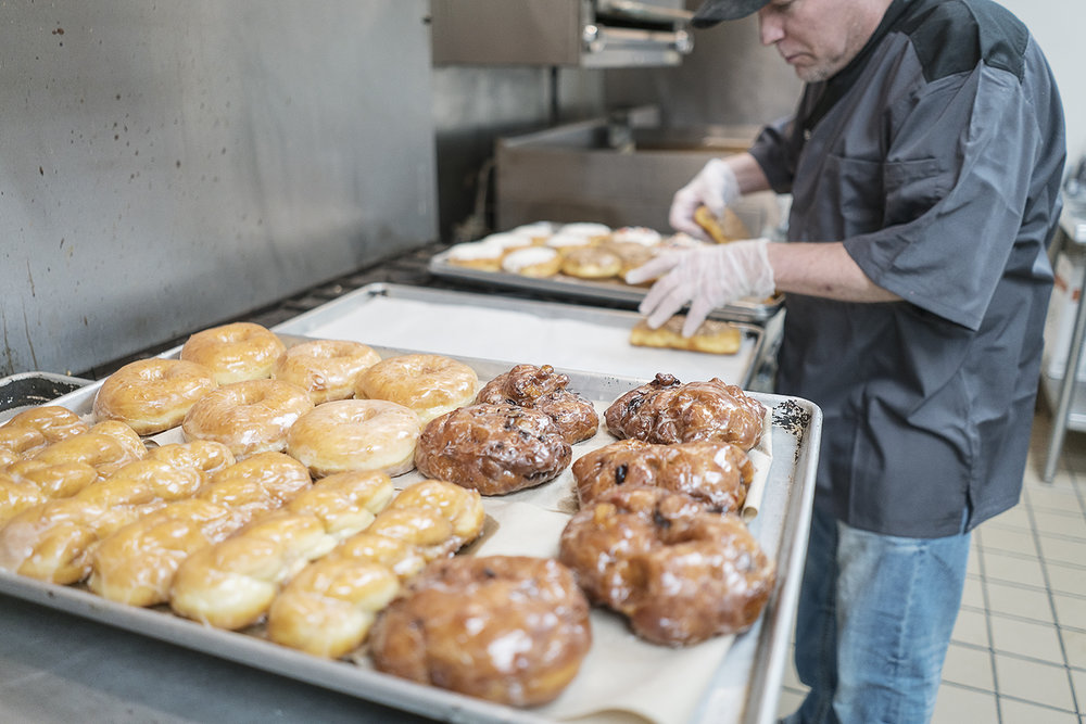 Flint, MI - Thursday, January 4, 2018: Bruce Sowles, 53, of Flint, transfers donuts to baking sheets before they are delivered to Foster's Coffee in downtown Flint at Blueline Donuts inside of Carriage Town Ministries.