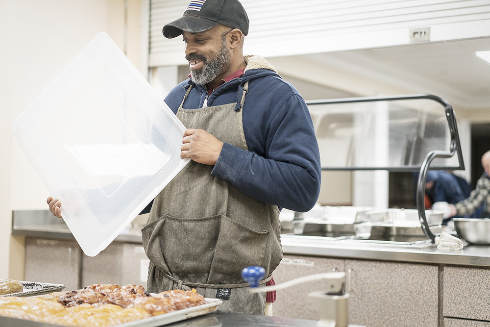Flint, MI - Thursday, January 4, 2018: Randall Thompson, 50, of Flint, smiles as he covers up fresh donuts for delivery at Blueline Donuts inside Carriage Town Ministries.