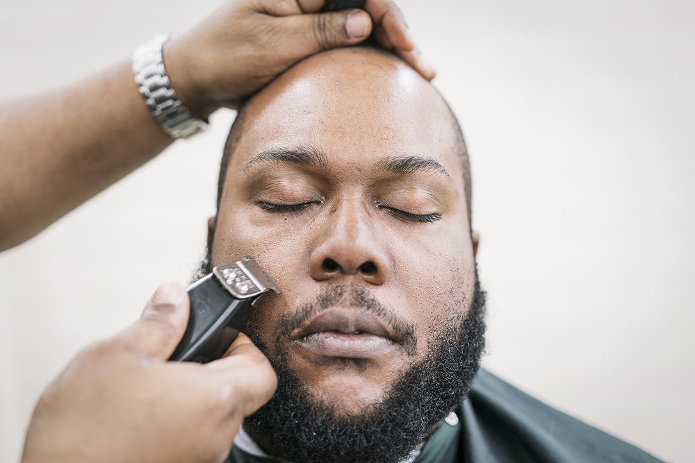 Flint, MI - Tuesday, February 6, 2018: Flint resident Brandon Ashley, 34, closes his eyes and relaxes while he receives a haircut and beard trim at the Flint Institute of Barbering.