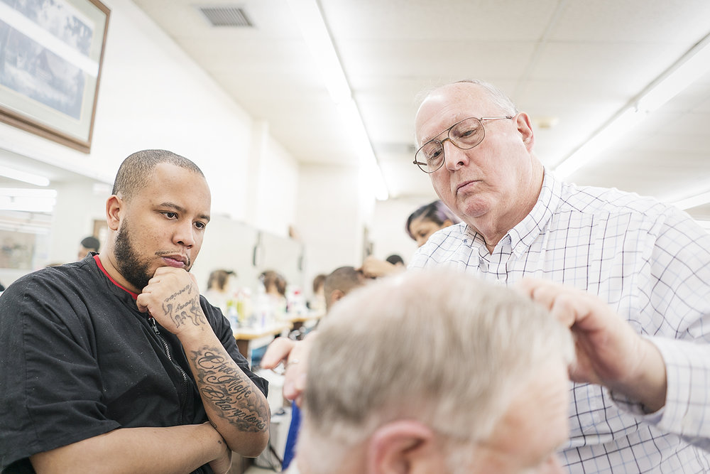 Flint, MI - Tuesday, February 6, 2018: Instructor Larry Woodby, 70, from Linden (right), examines a customer's cut by barber Chris Hampton, 29, from Flint, at the Flint Institute of Barbering.