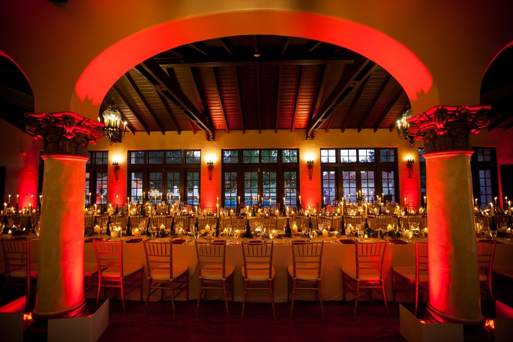 Uplighting is transformative. Long candles and red uplighting were all it took to set the mood at this client's Halloween wedding dinner.