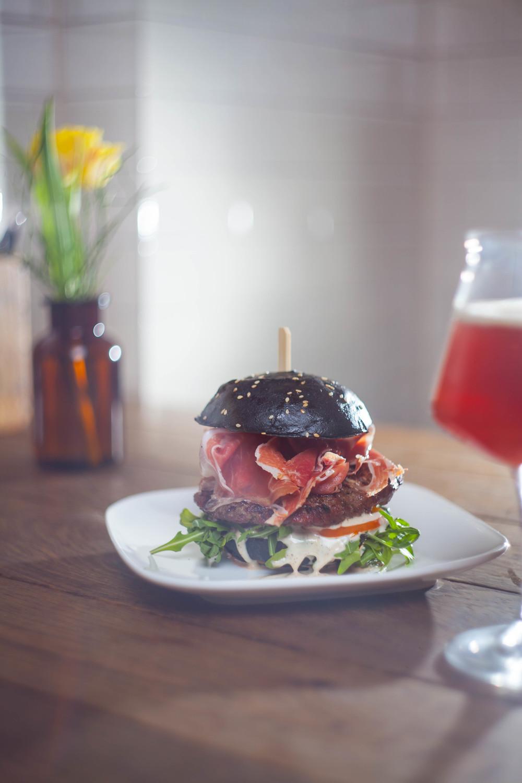 Die Fette Kuh in Köln überrascht mit schwarzem Brötchen, leckerem Serrano Schinken und Craft Beer.