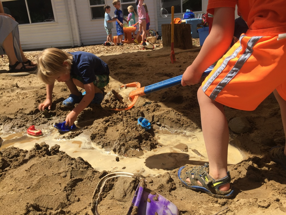Children thoroughly enjoy making rivers and channels with the water and mud in the sand box!