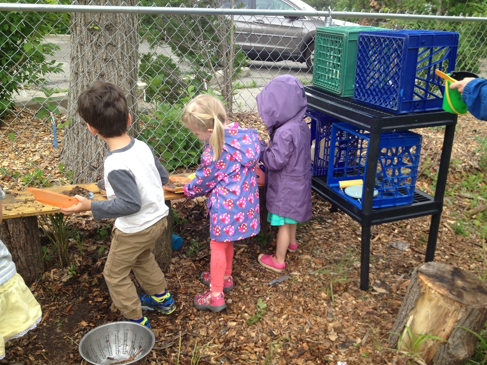 "The teachers constructed a ""mud kitchen"" using materials we already had: fence boards, stumps, shelving and crates, a sensory table tub for a sink, and pots, pans, utensils and dishes.  The children used it every day of camp to make meals and play house and restaurant."