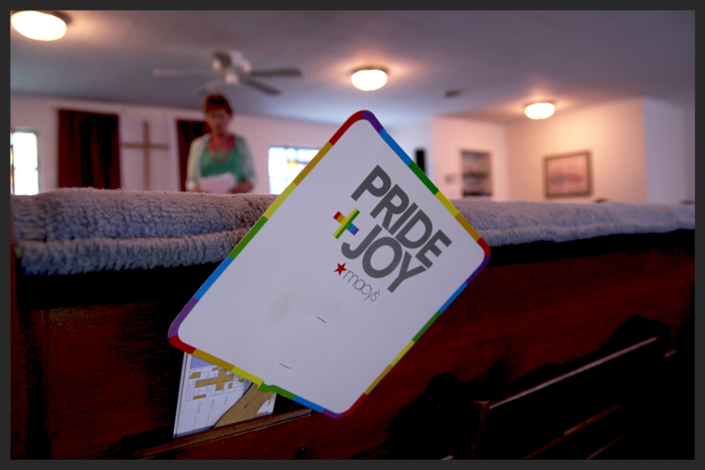 An LGBT themed paper fan rests in the back of an empty pew at Eternal Joy Metropolitan Community Church. Stacy Sandberg, who identifies as transgender, stands behind with a handful of papers.