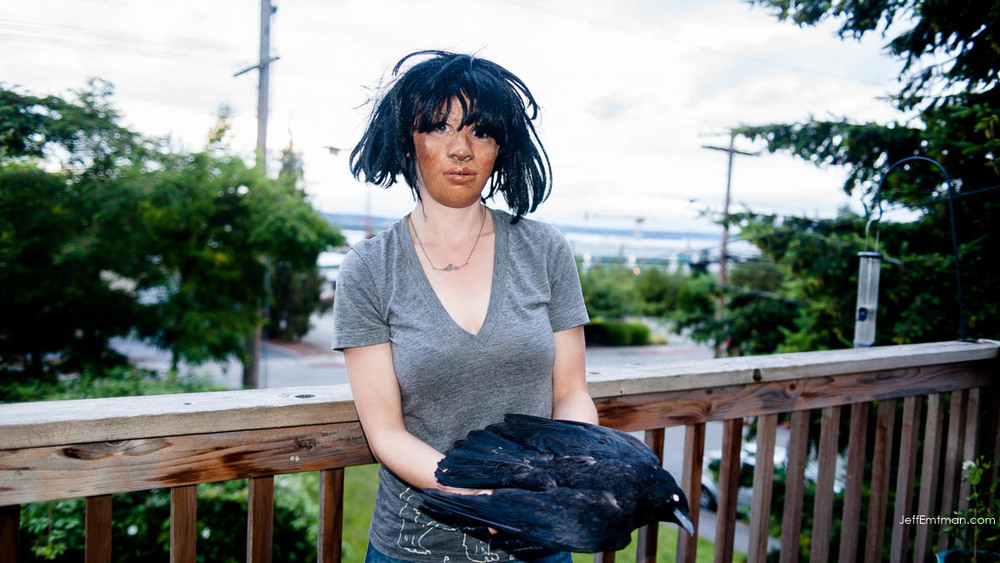 Kaeli Swift holds a stuffed crow while wearing a mask, replicating the pose used by her volunteers in a crow behavioral study.