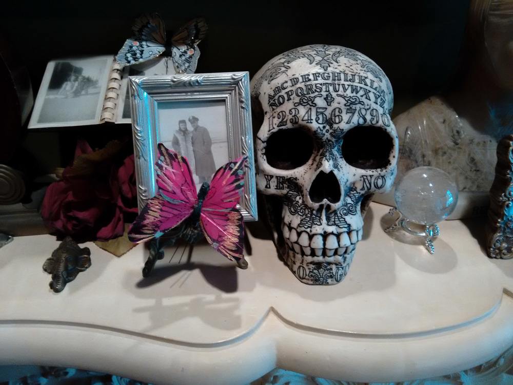 Ouija themed skull, family photo, crystal and butterfly.