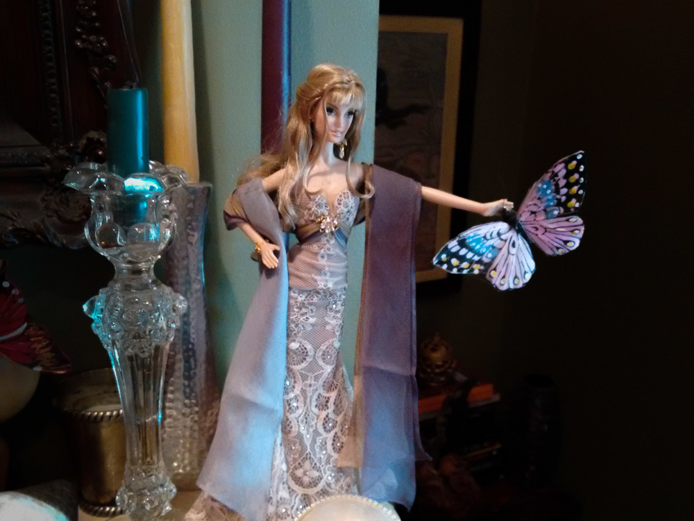 One of Patti's many Barbie dolls holding a butterfly.