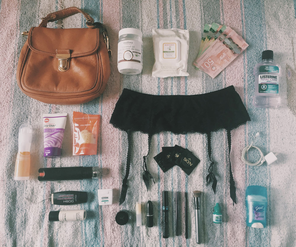 The contents of Remi's bag, laid on a bedsheet.  Contents include coconut oil, wet wipes, money, mouthwash, hosiery, lube, tampons, pepper spray / mace, condoms, cell phone charger, deoderant, eye drops, and cosmetics.