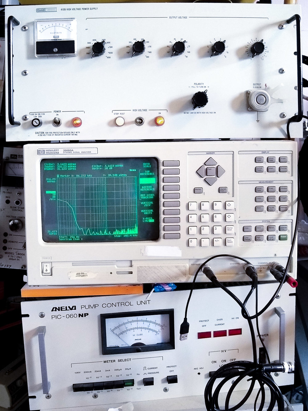 From top to bottom: a high voltage power supply, a dynamic signal analyzer, and a pump control unit.