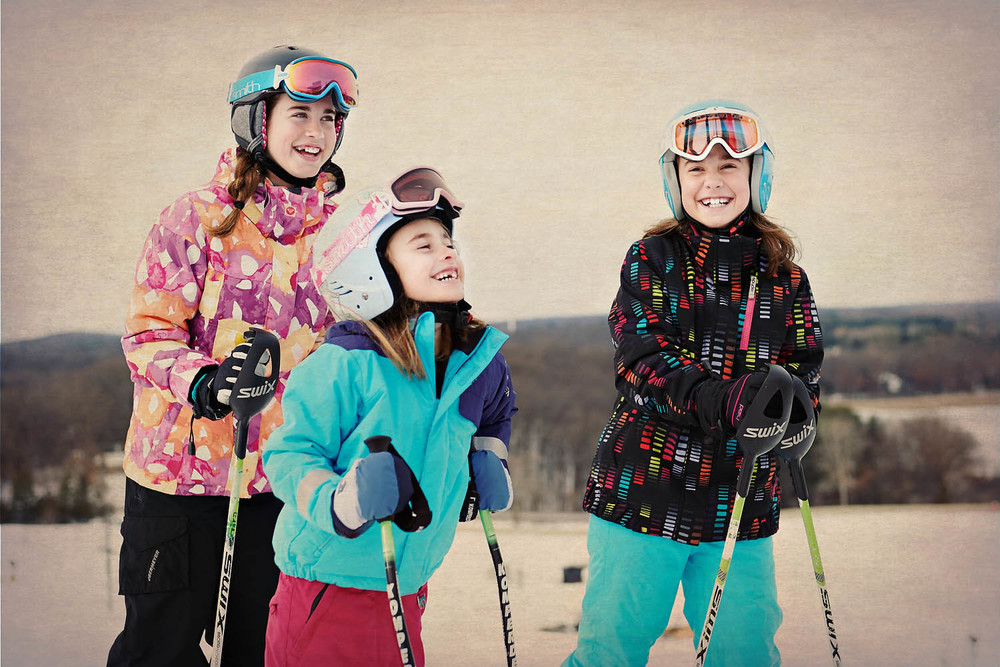 Group of kids laugh and enjoy skiing.